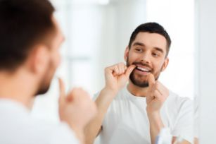 Man flossing in the mirror using tips from a dentist