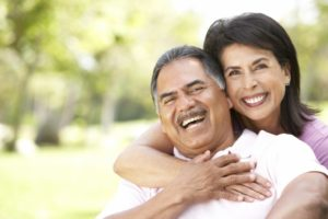 Smiling couple with dental implants in Goodlettsville outside in summer